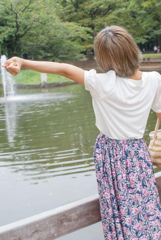 池の噴水に向かって手を広げる女の子