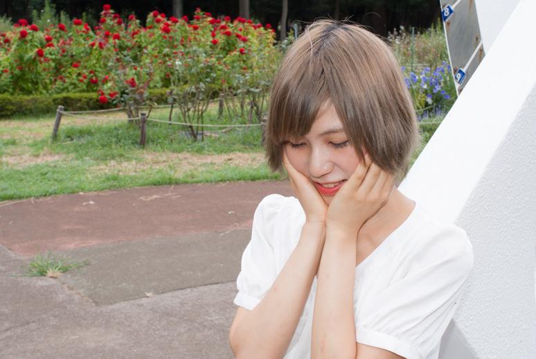代々木公園の日時計の前で顎に手を添える女の子
