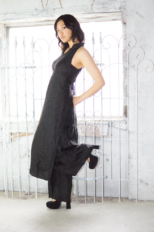 白い柵の前に立ち左足を上げる黒のドレスの女の子