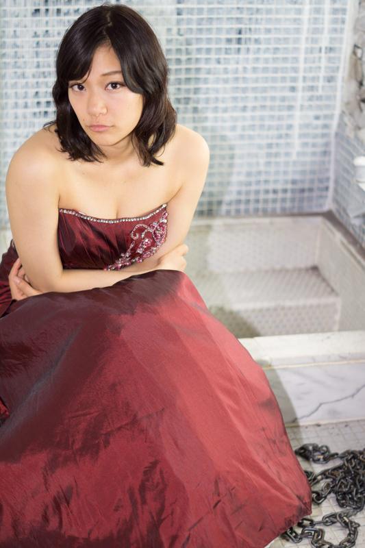 座ってこちらを見る赤いドレスの女の子と鎖