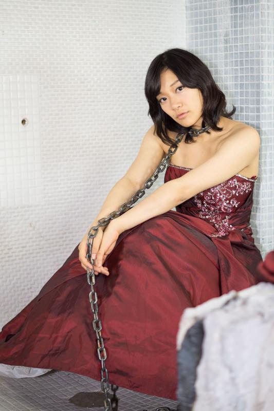 鎖を首にかけて座る赤いドレスの女の子