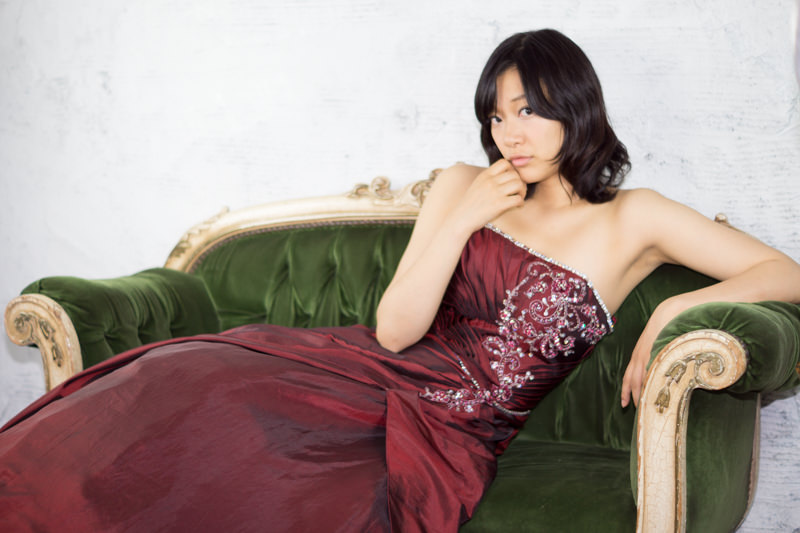 緑色の長いすに座る赤いドレスの女の子