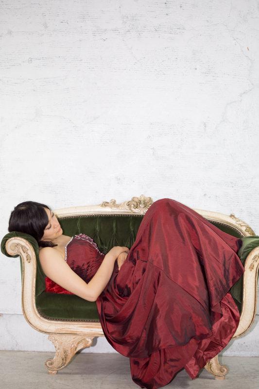 緑色の長いすで眠る赤いドレスの女の子