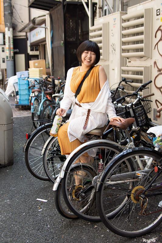 自転車置き場で笑う女性