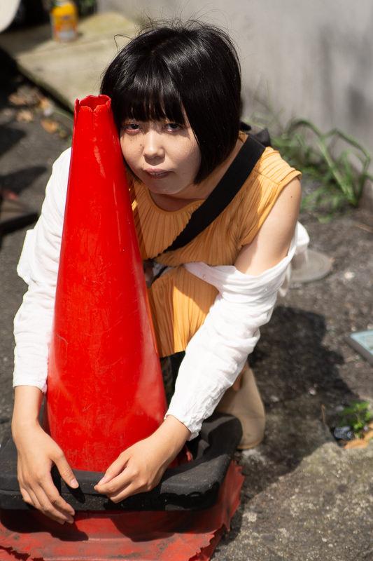 赤いカラーコーンを抱きかかえる女性