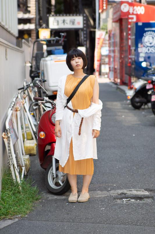 赤いバイクの前で立つ女性